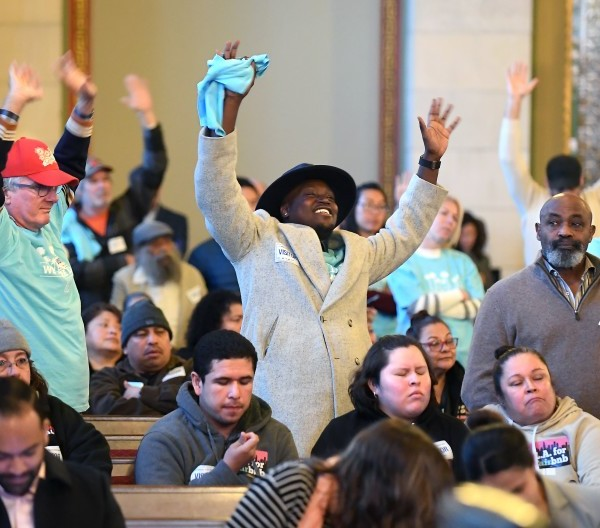 People who support legalizing and regulating short-term rentals of second homes wave their hands in agreement with a speaker during a Planning Commission meeting at Los Angeles City Hall on Dec. 19, 2019.(Credit: Wally Skalij / Los Angeles Times)