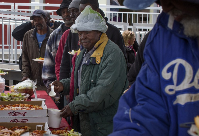 Residents of a new shelter in Watts receive plates full of pasta, pizza and salad during a Christmas lunch held on Dec. 23, 2019. The shelter cost $5.4 million to build. (Credit: Gabriella Angotti-Jones/Los Angeles Times)