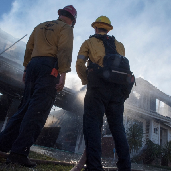 Firefighters hose down a burning house during the Tick Fire in Santa Clarita on Oct. 25, 2019. (Credit: Mark Ralston / AFP / Getty Images)