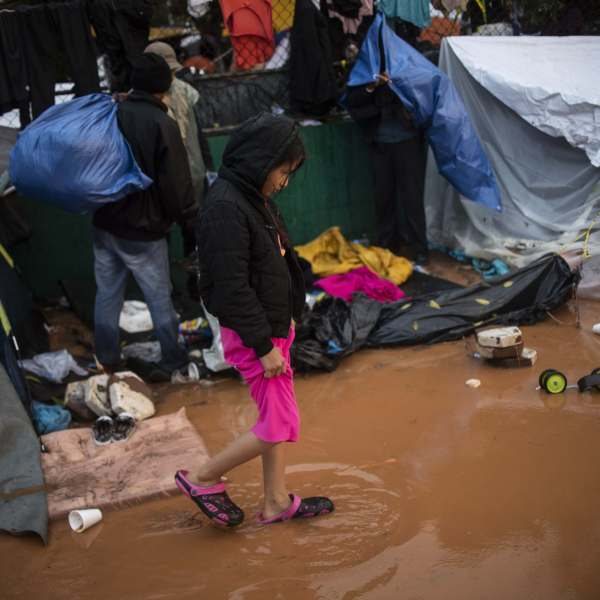 A migrant girl walks in the water at the temporary shelter in Tijuana near the U.S. border, after heavy rain on Nov. 29, 2018. (Credit: Pedro Pardo/AFP via Getty Images)