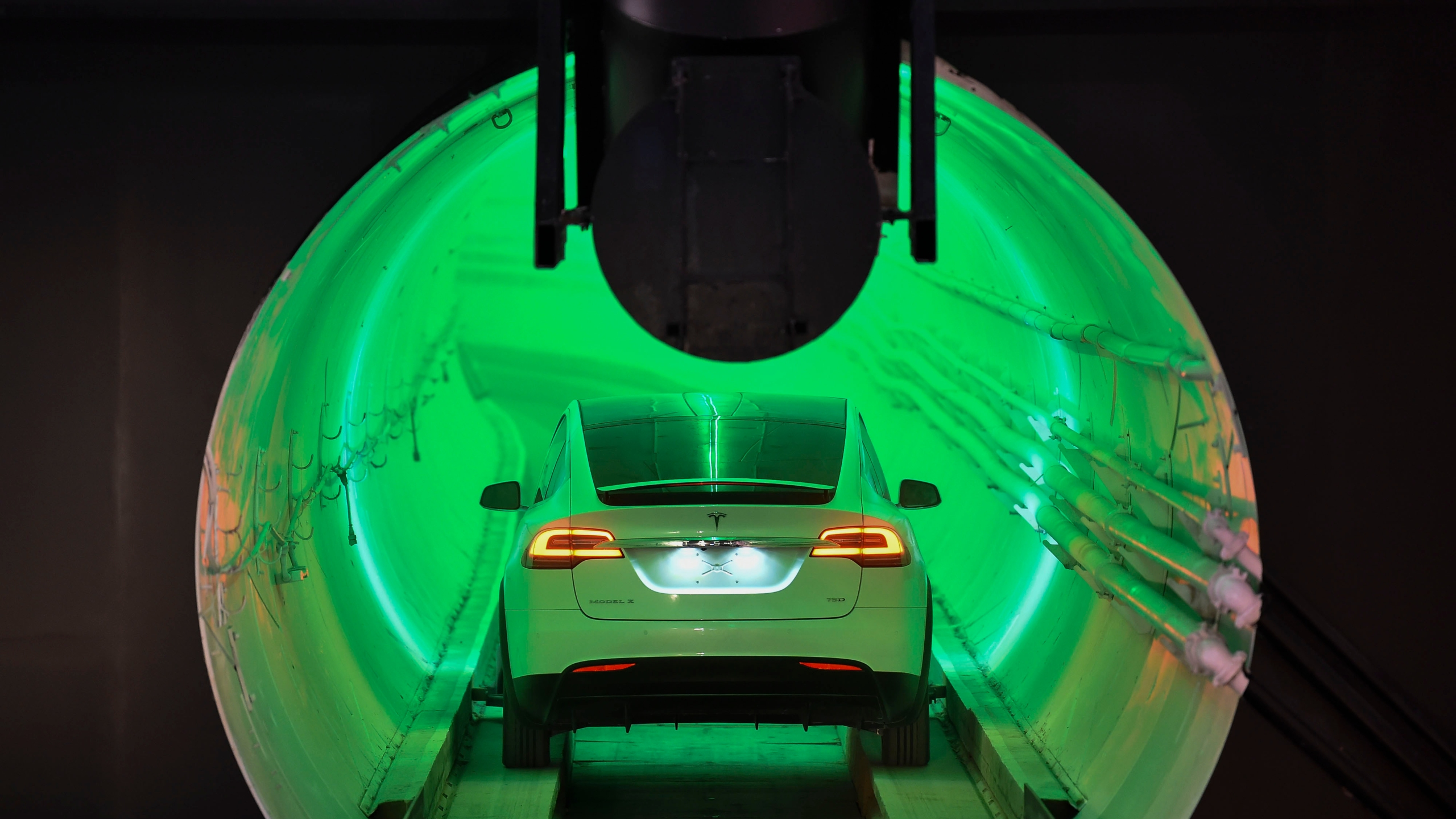 A modified Tesla Model X drives into the tunnel entrance before an unveiling event for the Boring Company Hawthorne test tunnel in Hawthorne, south of Los Angeles on Dec. 18, 2018. (Credit: ROBYN BECK/AFP via Getty Images)