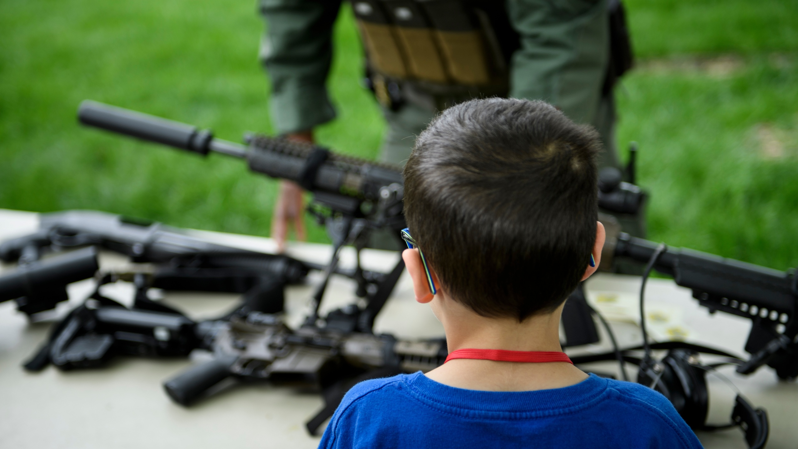 """A child looks at a rifle during a demonstration for """"Take Your Child to Work Day"""" at the Pentagon April 25, 2019, in Washington, D.C. (Credit: BRENDAN SMIALOWSKI/AFP via Getty Images)"""