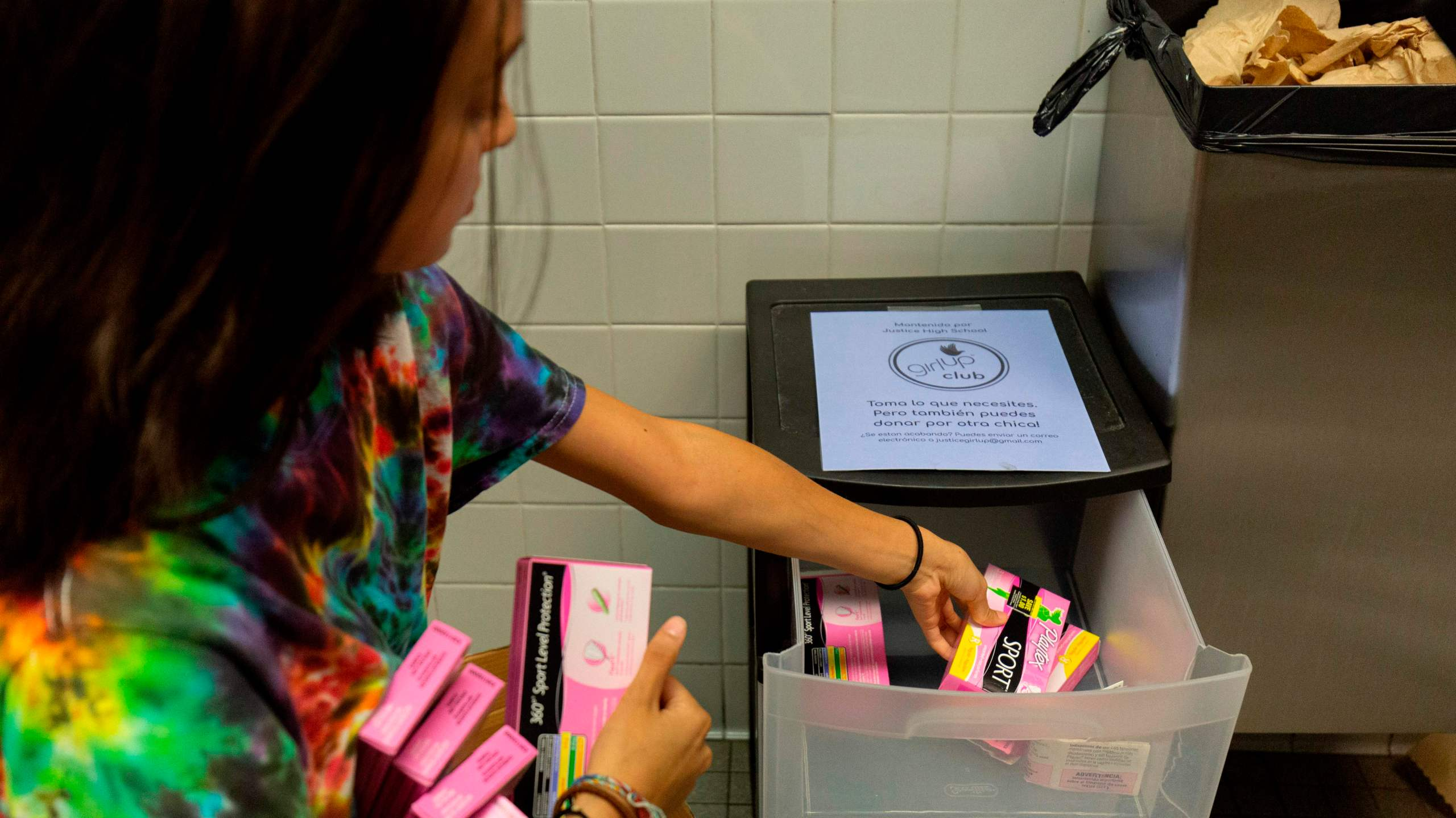 A student stocks a school bathroom with free pads and tampons to push for menstrual equity, at Justice High School in Falls Church, Virginia, on Sept. 11, 2019. (Credit: ALASTAIR PIKE/AFP via Getty Images)