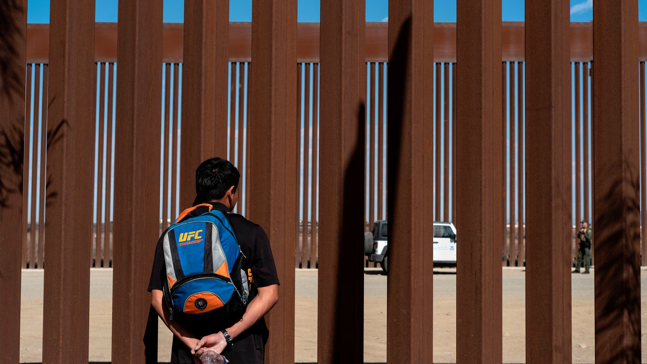 A migrant from Guatemala watches border patrol officers through the border fence at the Mexican side of the U.S.-Mexico border in Tijuana, Mexico, on Nov. 2, 2019. (Credit: Guillermo Arias/AFP via Getty Images)