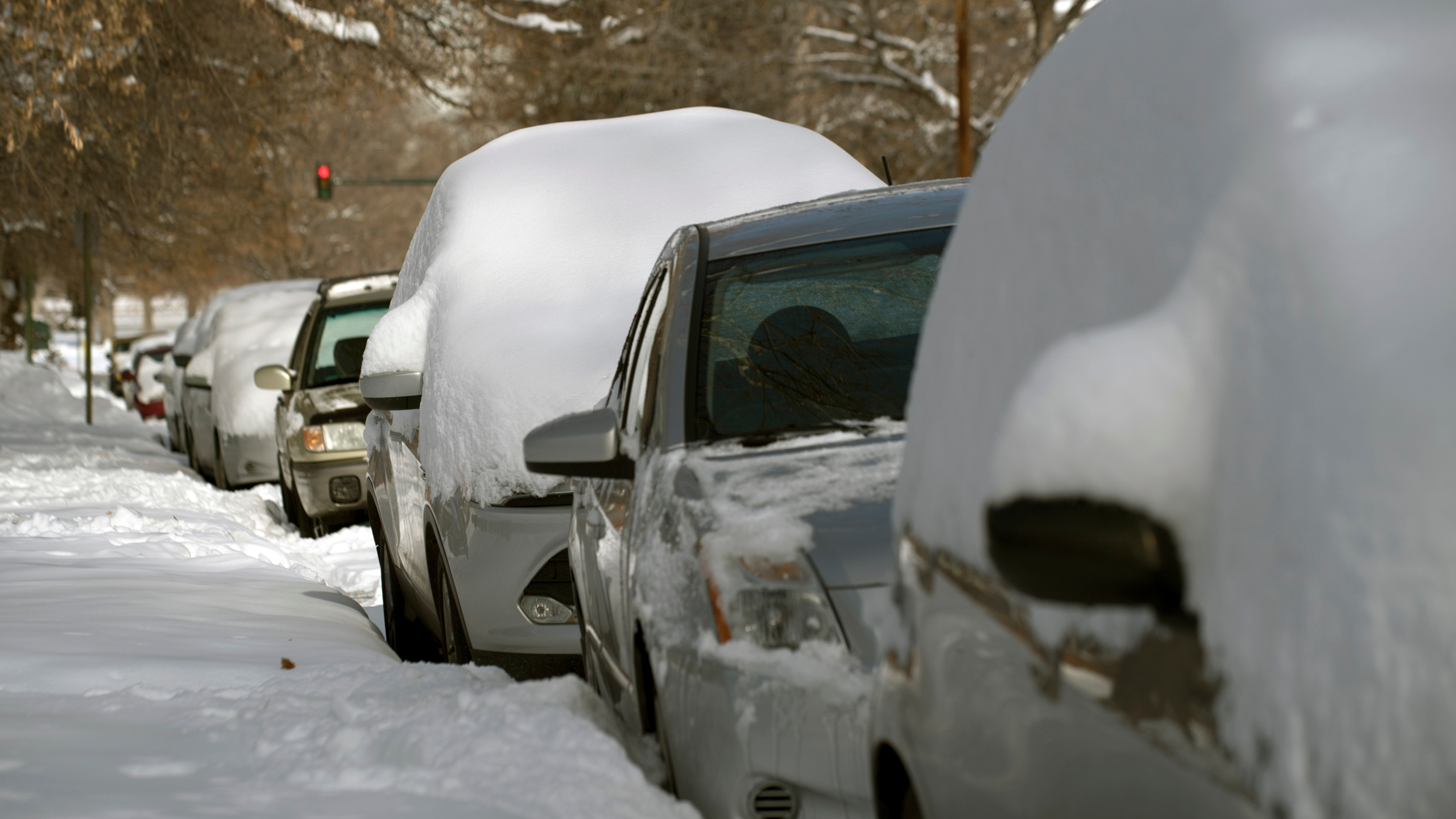 Cars lie buried under fresh snow in Denver, Colo. on Nov. 27, 2019. (Credit: JASON CONNOLLY/AFP via Getty Images)