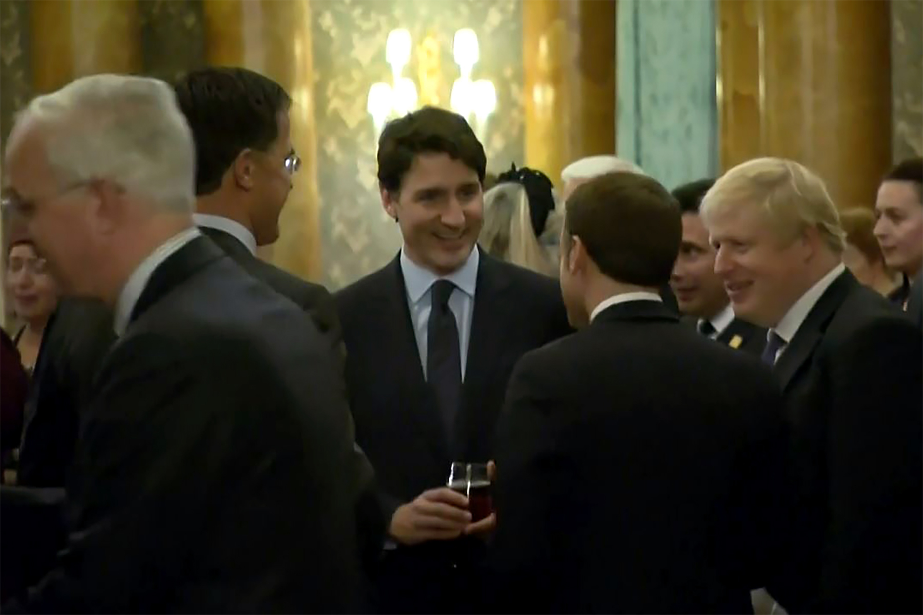 This screenshot from a video shows Dutch Prime Minister Mark Rutte, left, French President Emmanuel Macron, front, British Prime Minister Boris Johnson, right, and Canada's Prime Minister Justin Trudeau, back center, as the leaders of Britain, Canada, France and the Netherlands were caught on camera at a Buckingham Palace reception talking about President Donald Trump's lengthy media appearances ahead of the NATO summit on Dec. 3, 2019 in London. (Credit: NATO TV/AFP via Getty Images)