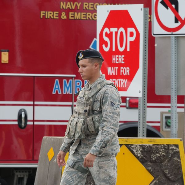A guard walks past a naval emergency ambulance responding to a fatal shooting at the Pearl Harbor Naval Shipyard in Honolulu, Hawaii, on Dec. 4, 2019. (Credit: Ronen Zilberman / AFP / Getty Images)