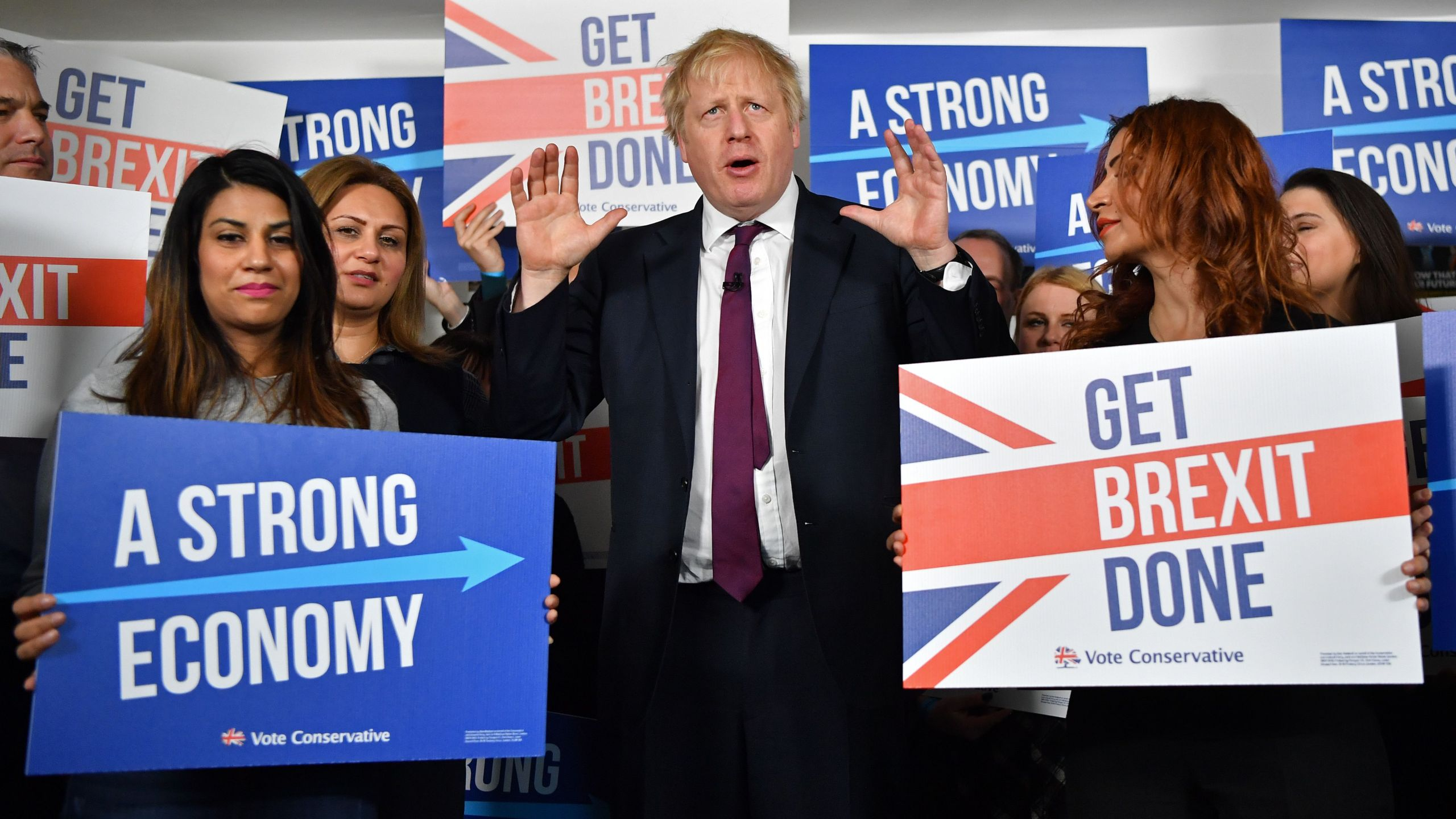 Britain's Prime Minister Boris Johnson speaks to activists and supporters as he poses for a photograph at the Conservative Campaign Headquarters Call Centre in central London on Dec. 8, 2019. (Credit: BEN STANSALL/POOL/AFP via Getty Images)
