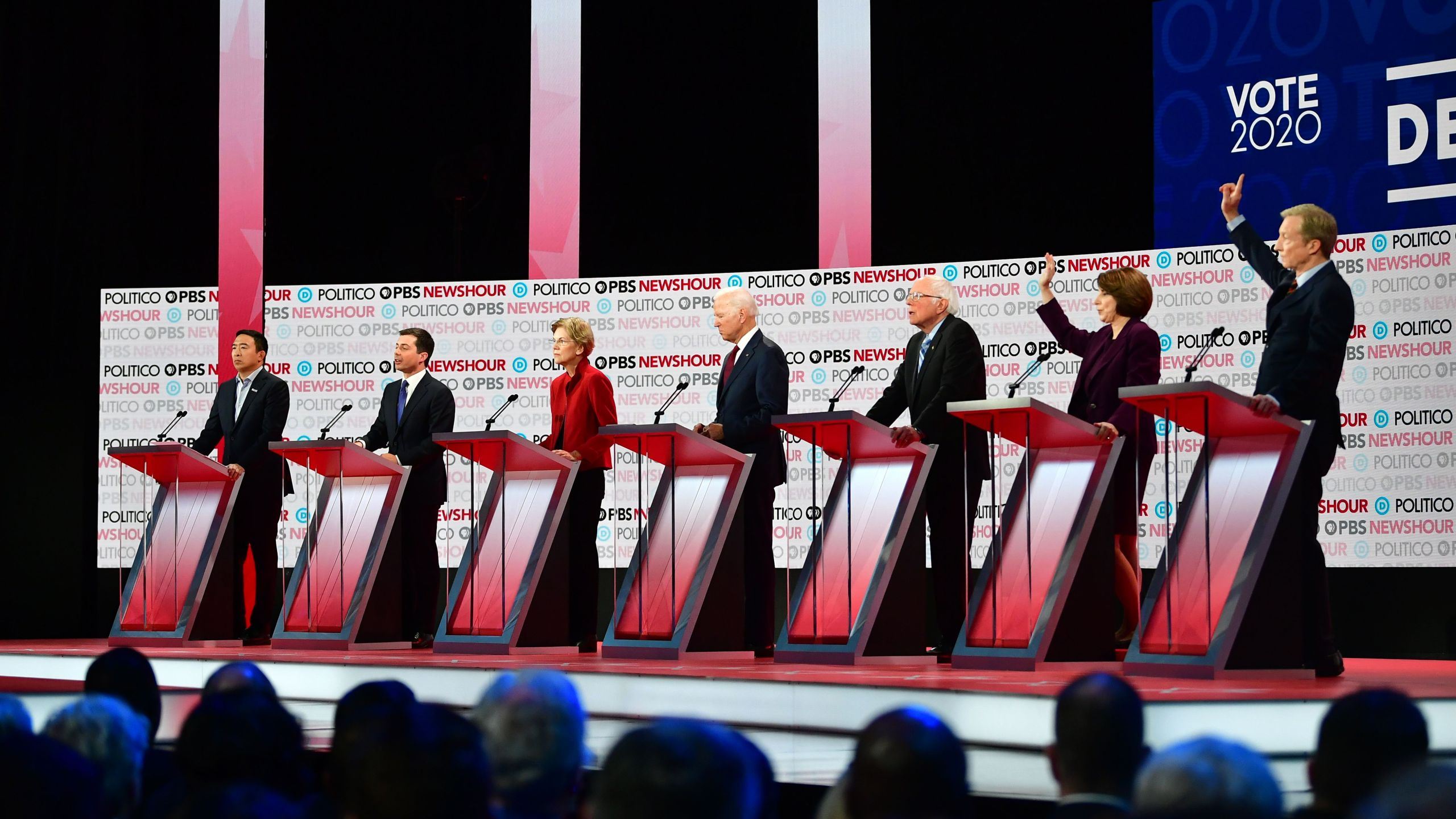 From left, Democratic presidential hopefuls entrepreneur Andrew Yang, South Bend Mayor Pete Buttigieg, Massachusetts Sen. Elizabeth Warren, former Vice President Joe Biden, Vermont Sen. Bernie Sanders, Minnesota Sen. Amy Klobuchar and businessman Tom Steyer participate at the sixth Democratic primary debate at Loyola Marymount University on Dec. 19, 2019. (Credit: Frederic J. Brown / AFP / Getty Images)