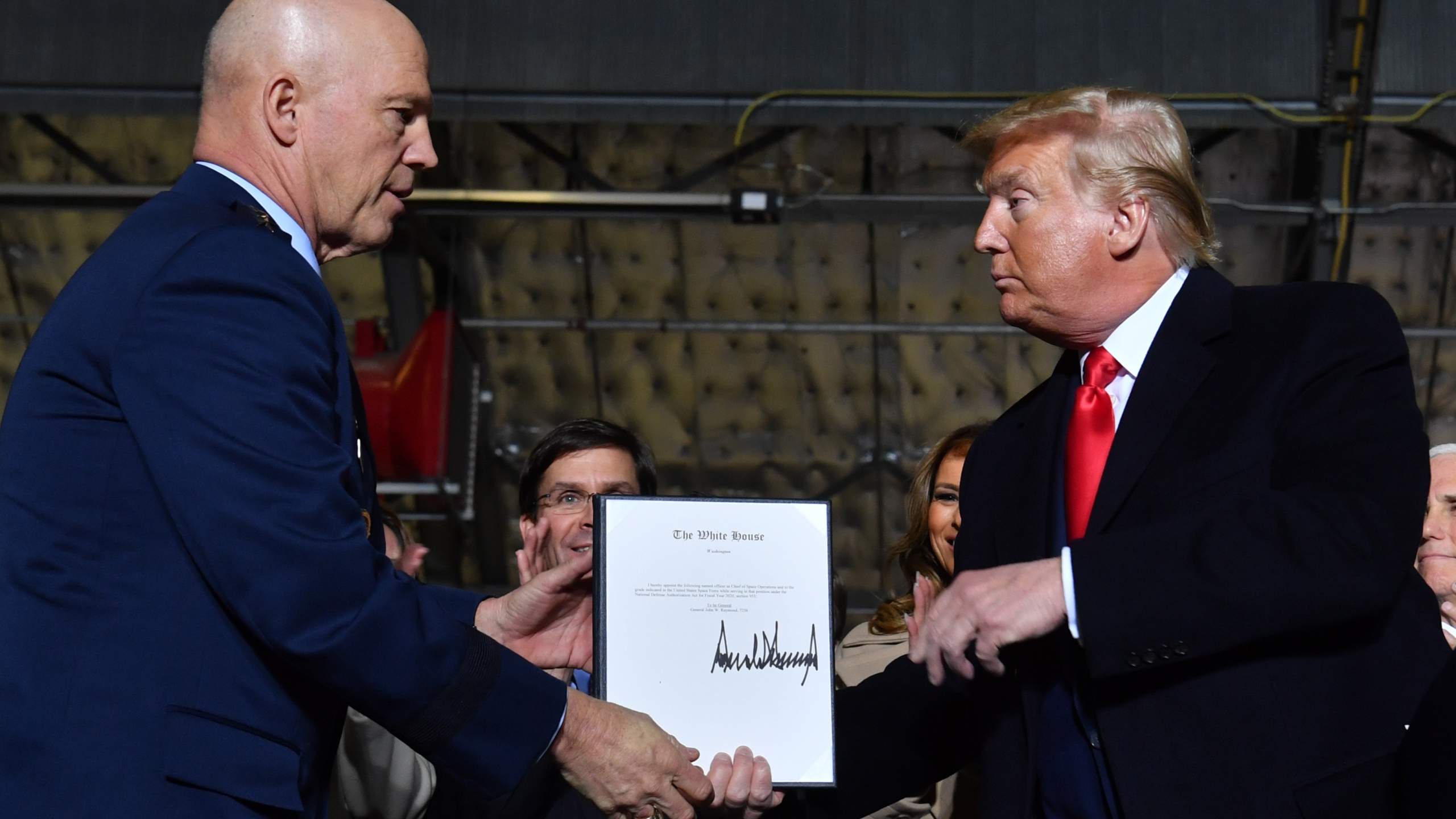 President Donald Trump, right, hands General John W. Raymond a document after signing the National Defense Authorization Act at Joint Base Andrews, Maryland, on Dec. 20, 2019. (Credit: Nicholas Kamm / AFP / Getty Images)