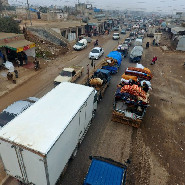 This aerial view taken on Dec. 24, 2019, in the village of Hazano, about 20 kilometers northwest of the city of Idlib, shows Syrian families from the south of Idlib province driving through the town towards the Syrian-Turkish border as they flee from the assault led by government forces and their allies. (Credit: Aref TAMMAWI/ Getty Images)