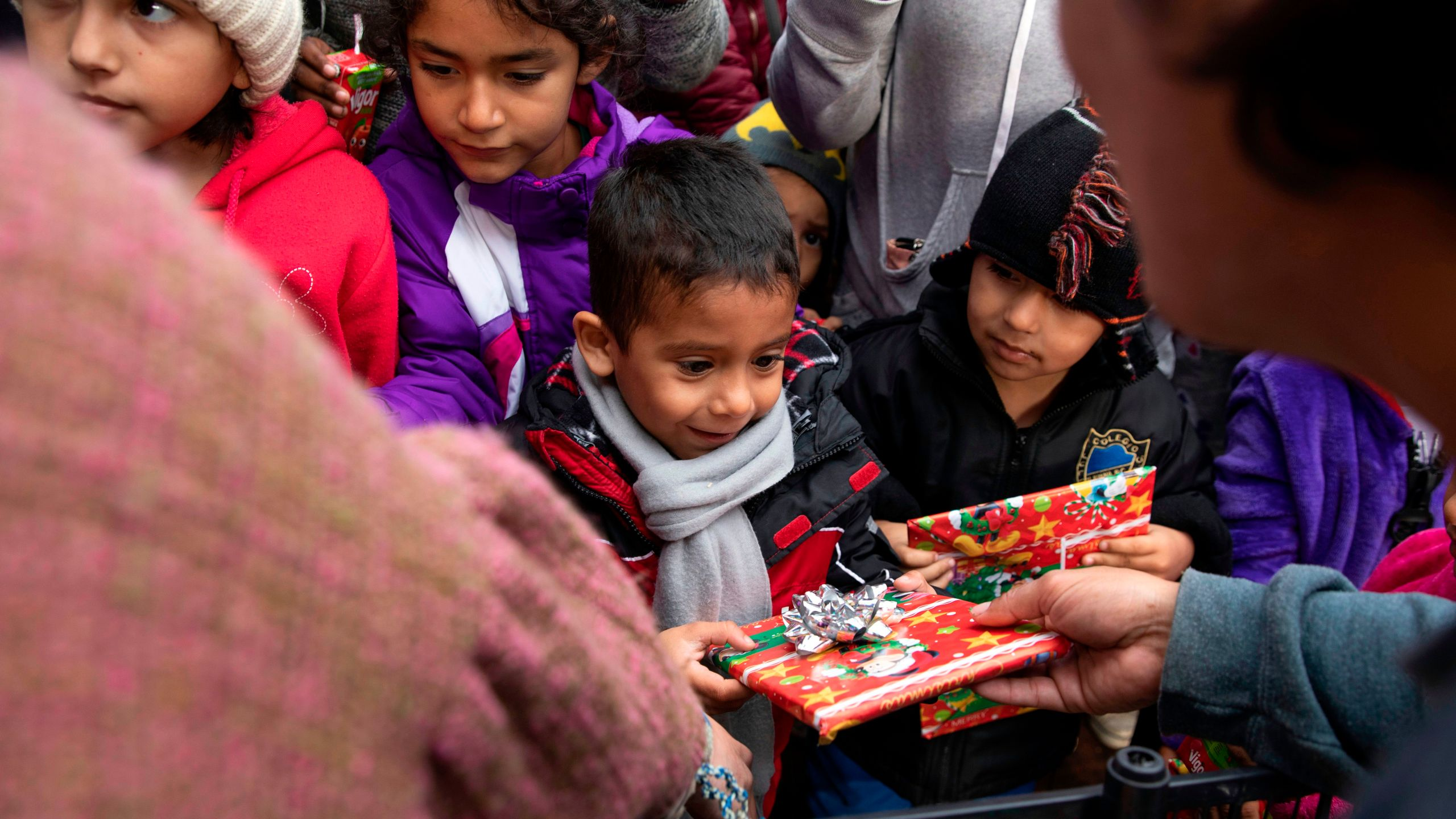 Migrant children receive Christmas presents from a group of law students from California as they wait for humanitarian visas from U.S. migration authorities outside El Chaparral port of entry, in Tijuana on Dec. 24, 2019. (Credit: EDUARDO JARAMILLO CASTRO/AFP via Getty Images)