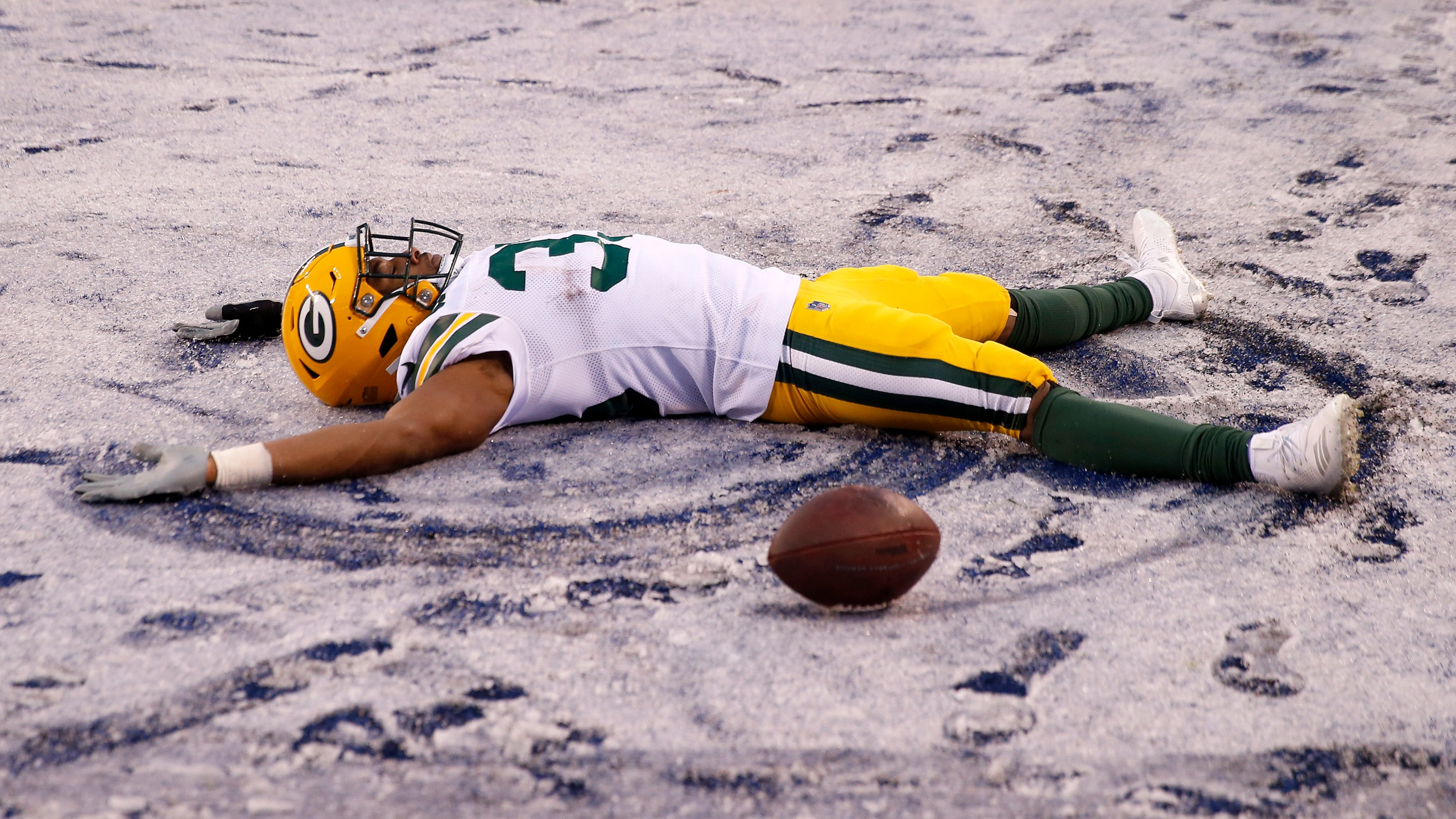 Aaron Jones #33 of the Green Bay Packers makes a snow angel in the end zone in the fourth quarter against the New York Giants at MetLife Stadium on Dec. 1, 2019 in East Rutherford, New Jersey. (Credit: Elsa/Getty Images)