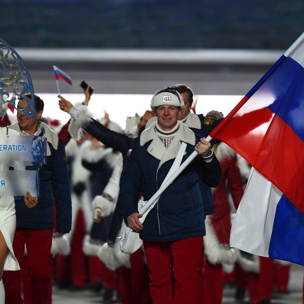 Bobsleigh racer Alexander Zubkov of the Russia Olympic team carries his country's flag alongside model Irina Shayk (left) during the Opening Ceremony of the Sochi 2014 Winter Olympics at Fisht Olympic Stadium on February 7, 2014 in Sochi, Russia. (Credit: Pascal Le Segretain/Getty Images)