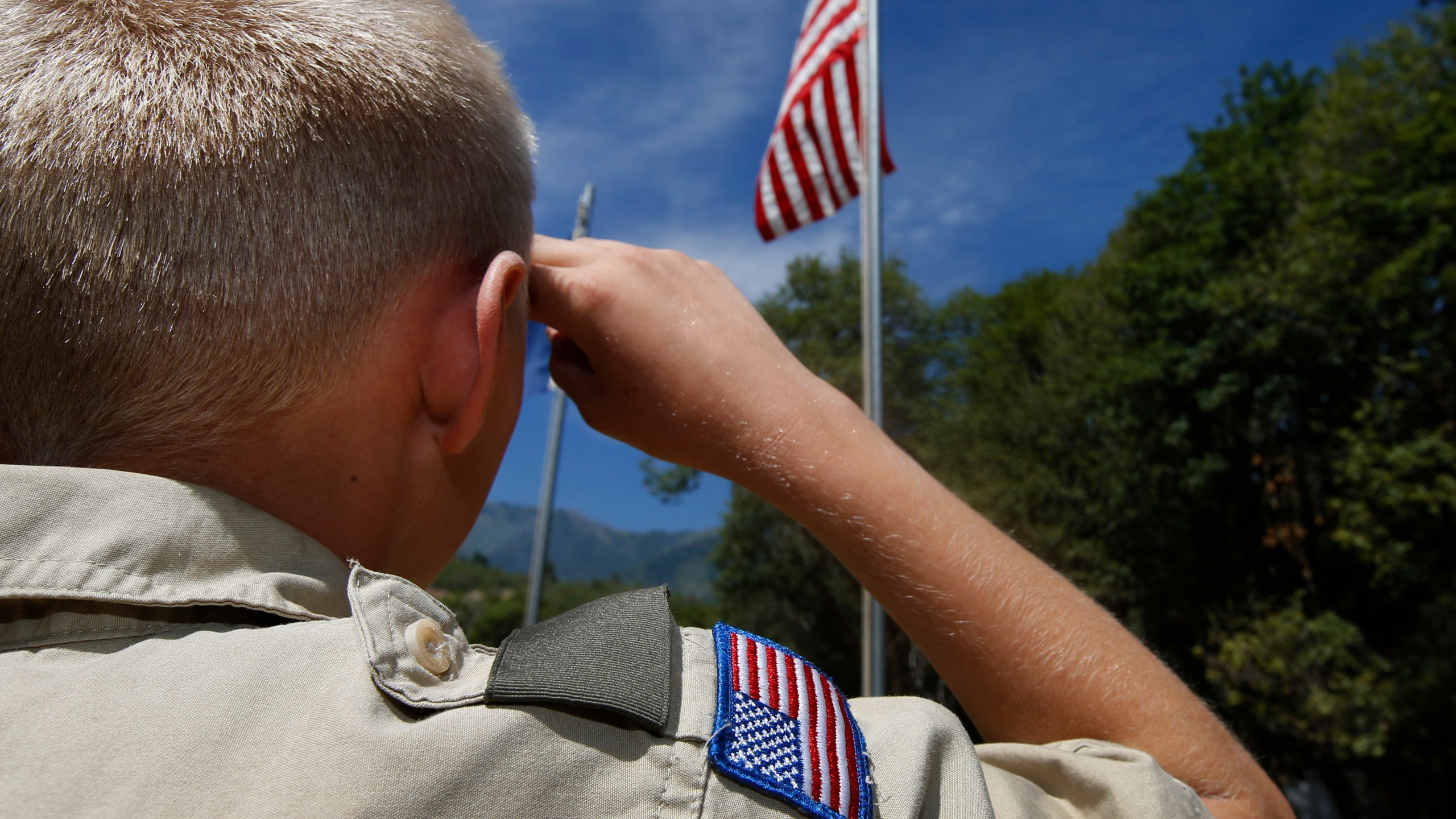 A Boy Scout salutes the American flag at camp Maple Dell on July 31, 2015, outside Payson, Utah. (Credit: George Frey/Getty Images)