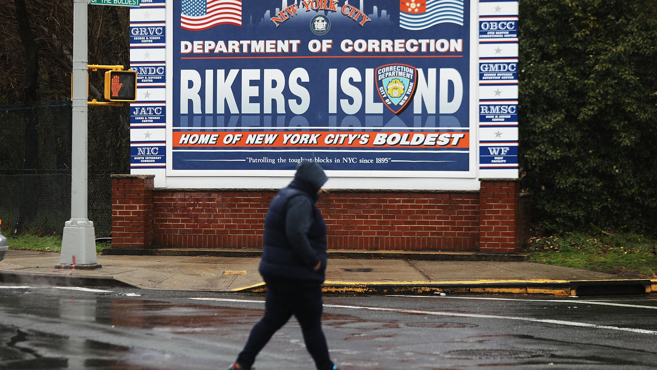 A woman walks by a sign at the entrance to Rikers Island on March 31, 2017 in New York City. (Credit: Spencer Platt/Getty Images)