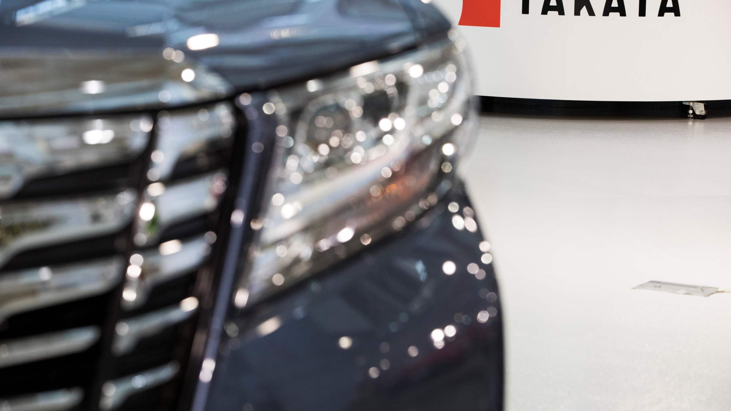 Logo of the Japanese auto parts maker Takata is seen next to a car at a showroom in Tokyo on June 23, 2017.(Credit: BEHROUZ MEHRI/AFP via Getty Images)
