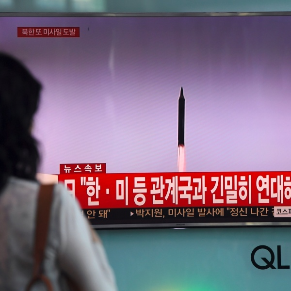 A woman watches a screen showing file footage of a North Korean missile launch, at a railway station in Seoul on September 15, 2017. (Credit: JUNG YEON-JE/AFP via Getty Images)