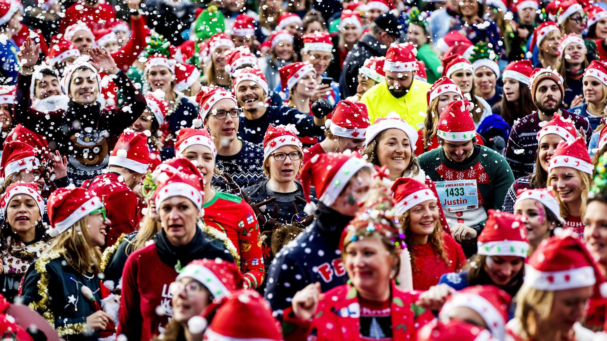 People take part in an Ugly Christmas Sweater Run on December 16, 2017, in The Vondelpark in Amsterdam. (Credit: KOEN VAN WEEL/AFP via Getty Images)