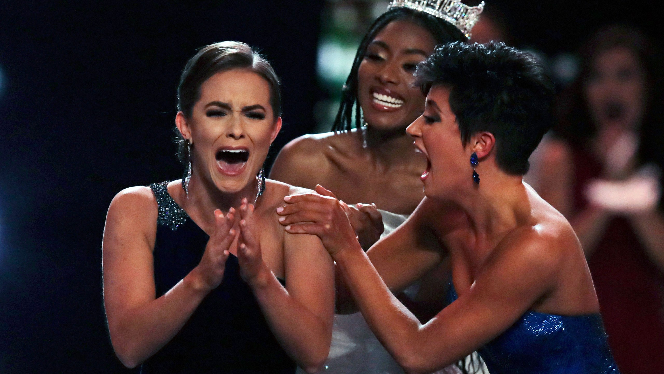 Camille Schrier, of Virginia, left, reacts after winning the Miss America competition at the Mohegan Sun casino in Uncasville, Conn., Thursday, Dec. 19, 2019. At right is runner-up Miss. Georgia Victoria Hill and and at rear is 2019 Miss. America Nia Franklin. (AP Photo/Charles Krupa, via CNN)