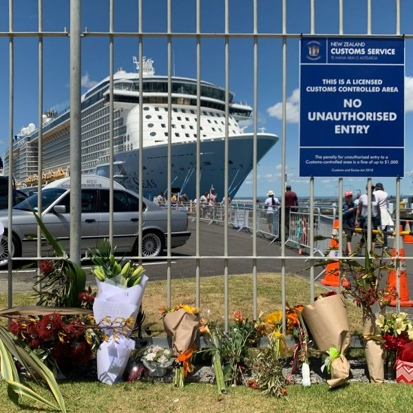 Flowers are laid at a makeshift memorial seen in front of cruise ship Ovation of the Seas, in Tauranga, New Zealand on December 10, 2019. (Credit: Nick Perry/AP via CNN Wire)