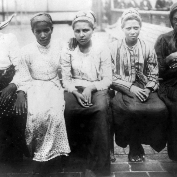 Five newly arrived Immigrants sit on a dock at Ellis Island in 1910. (Credit: Library of Congress via CNN)