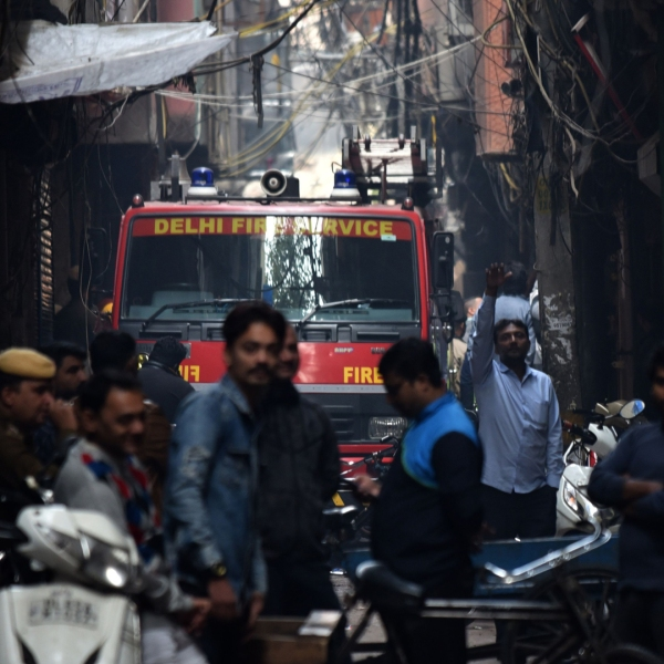 A Delhi Fire Service truck is seen along a street near the site of a facotry where a fire broke out, in Anaj Mandi area of New Delhi on December 8, 2019. (Credit: STR/AFP via Getty Images)