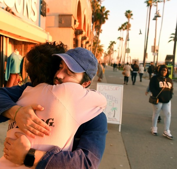 """Jody Monkarsh's sons Henry, left, and Sam hug outside Jody Maroni's Sausage Kingdom on the Venice boardwalk during a """"final celebration"""" after 40-years in business in December 2019. (Credit: Wally Skalij/Los Angeles Times)"""