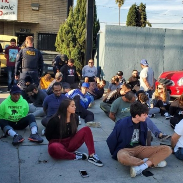Subjects sit on the ground with their hands zip-tied following an unlicensed dispensary raid in Palms on Dec. 12, 2019. (Credit: California Bureau of Cannabis Control via Los Angeles Times)
