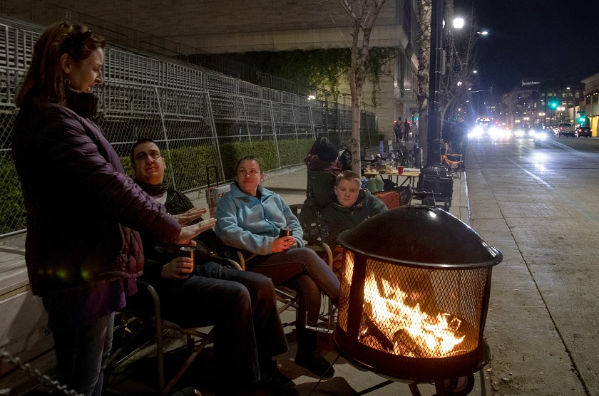 Denise Koehnlein of Phoenix, left, stays warm by the fire while chatting with Mark Breiling, Quisha Ryan and Christian Ryan as they camp and wait for the 2020 Rose Parade on Dec. 31, 2019. (Credit: Gina Ferazzi/ Los Angeles Times)