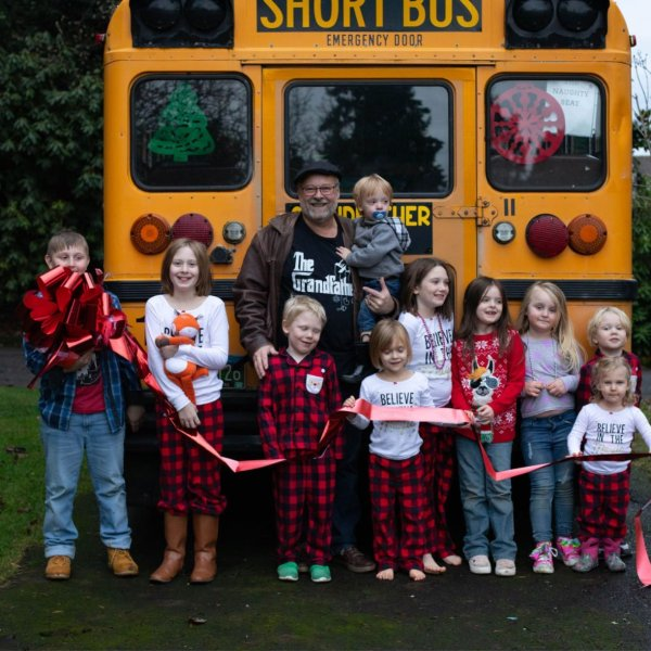 Doug Hayes of Oregon poses with his grandchildren and the bus he bought them for Christmas in 2019. (Credit: Amy Hayes via CNN)