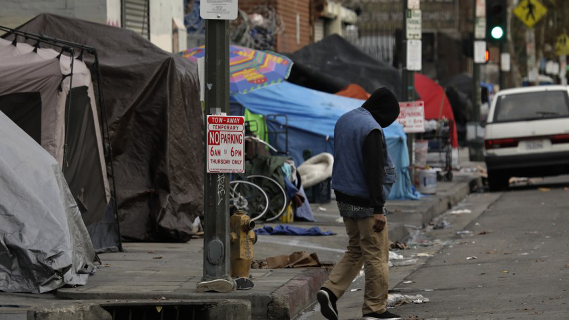 A man walks down 6th Street, weaving his way around tents, in Los Angeles.(Credit: Carolyn Cole/Los Angeles Times)