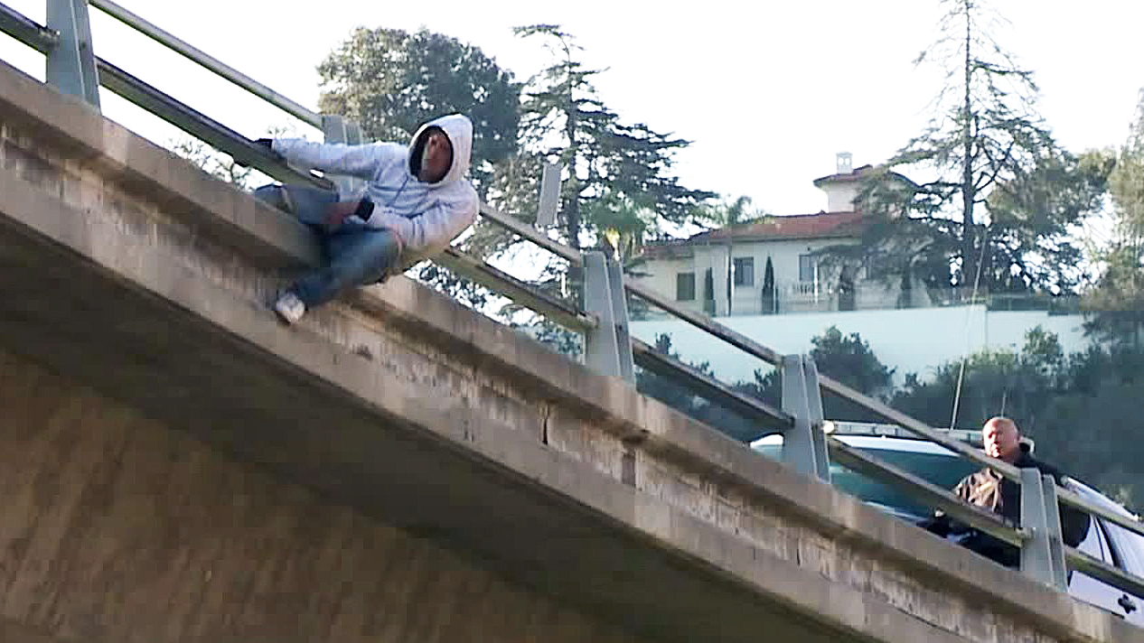 A man dangles from a freeeway overpass in San Diego during a long standoff with police on Dec. 6, 2019. (Credit: KTLA)