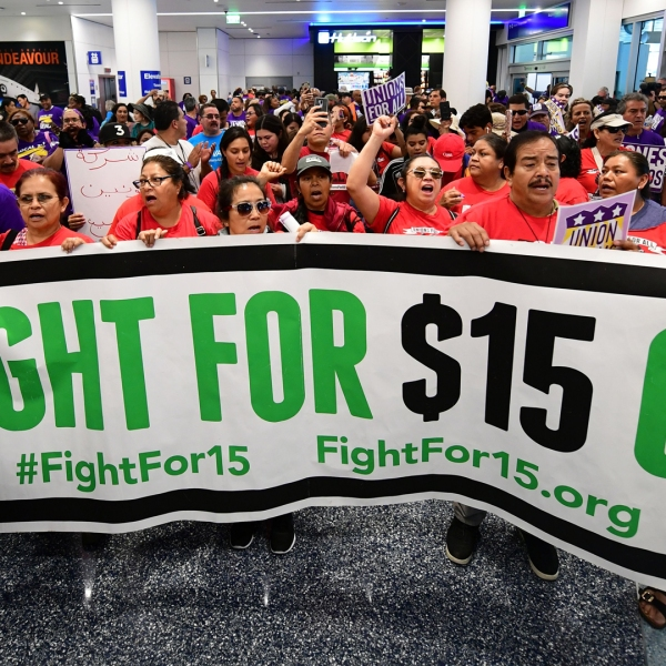 A banner for a $15 dollar per hour minimum wage is displayed as airport employees are joined by drivers from Uber and Lyft and other southern California workers for a protest at Los Angeles International Airport October 2, 2019. (Credit: FREDERIC J. BROWN/AFP via Getty Images)
