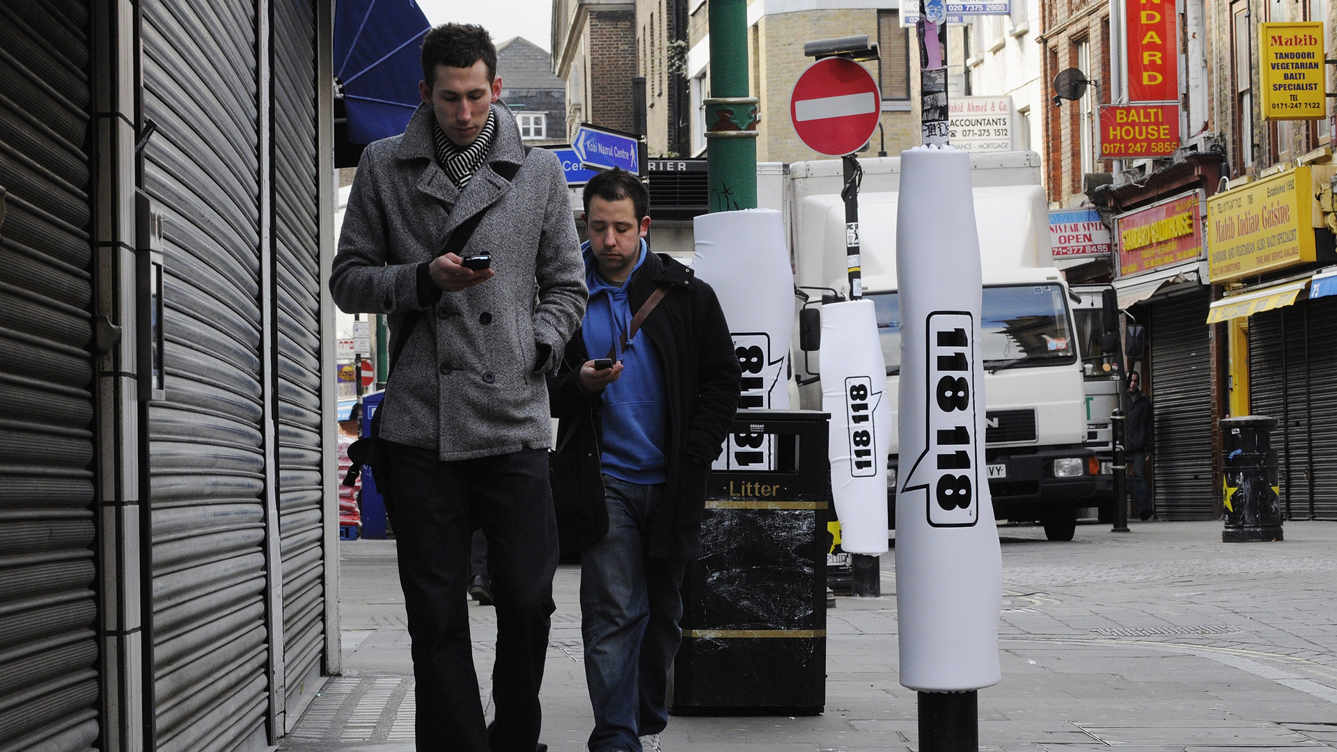 Two pedestrians walks past padded lamp posts whilst texting in Brick Lane on March 4, 2008, in London, England. (Credit: Micha Theiner/Getty Images)