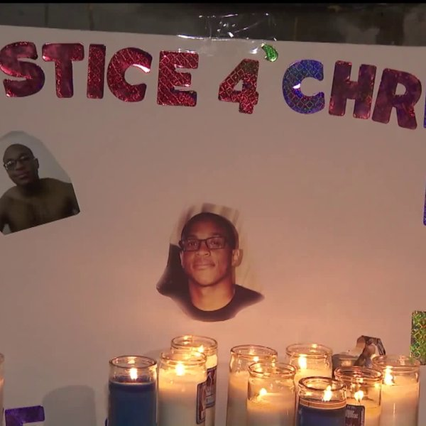 A sign is displayed during a vigil held Dec. 9, 2019, one year after Christopher Mitchell was shot and killed by Torrance police. (Credit: KTLA)