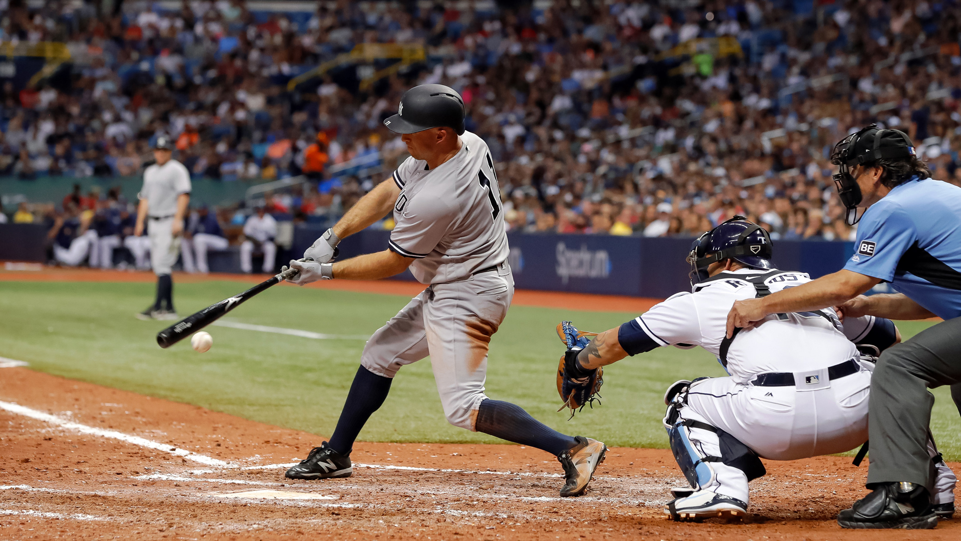 Brett Gardner #11 of the New York Yankees singles in front of Wilson Ramos #40 of the Tampa Bay Rays and umpire Phil Cuzzi #10 in the seventh inning of a baseball game at Tropicana Field on June 22, 2018 in St. Petersburg, Florida. (Credit: Mike Carlson/Getty Images)