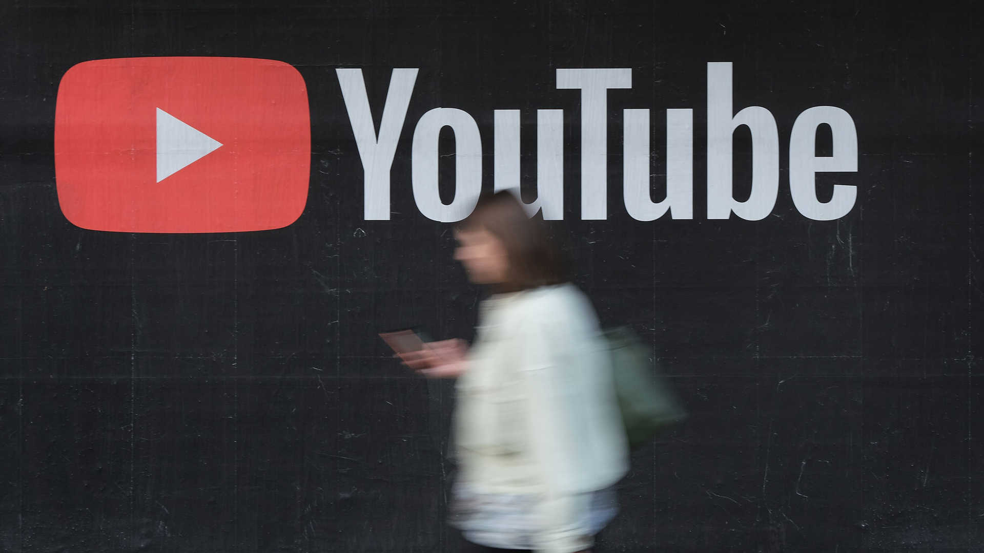 A person is seen walking in front of a YouTube sign in this file photo. (Credit: Sean Gallup/Getty Images)