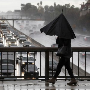 A woman walks in the rain with a broken umbrella during a December 2019 storm in Encino. (Credit: Mel Melcon / Los Angeles Times)