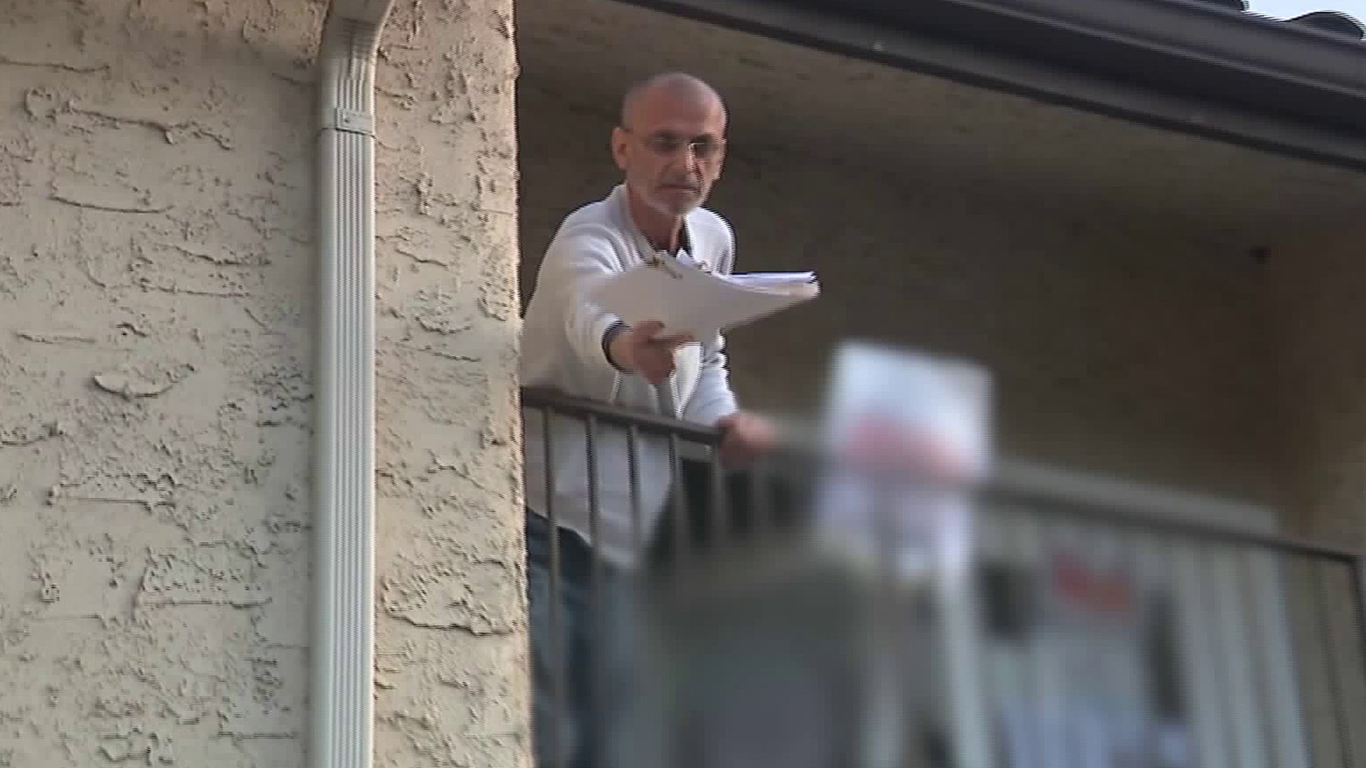 """A man drops papers down to reporters while shouting, """"Call the White House,"""" on Jan. 15, 2020. (Credit: KTLA)"""