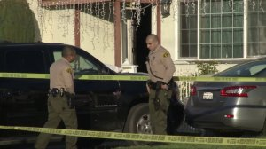 Deputies stand outside a Compton home after a shooting that left a woman dead and a man in critical condition on Jan. 1, 2020. (Credit: KTLA)