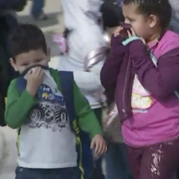 Students cover their noses after a Delta flight dropped fuel over the playground of Park Avenue Elementary School in Cudahy on Jan. 14, 2020. (Credit: KTLA)