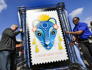 Michael Henry, left, and Charles Williams of the U.S. Postal Service with a replica of the Year of the Rat stamp at the Lunar New Year Festival in Monterey Park.(Credit: Irfan Khan / Los Angeles Times)