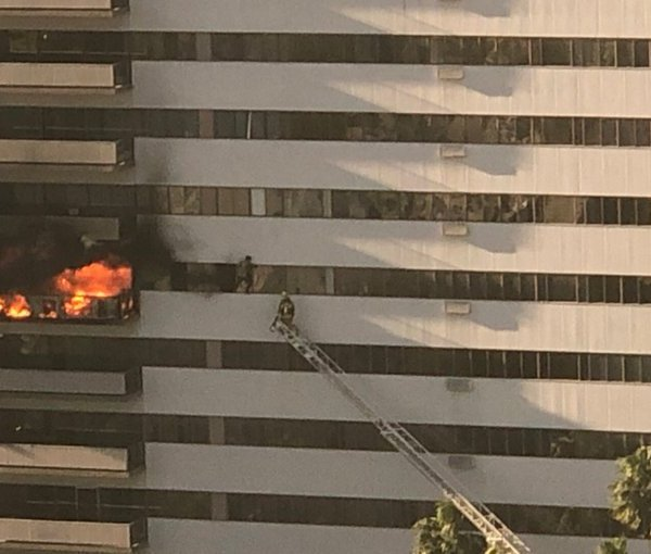 LAFD tweeted this image of a firefighter working to a rescue someone hanging outside Barrington Plaza amid a fire on Jan. 29, 2020.