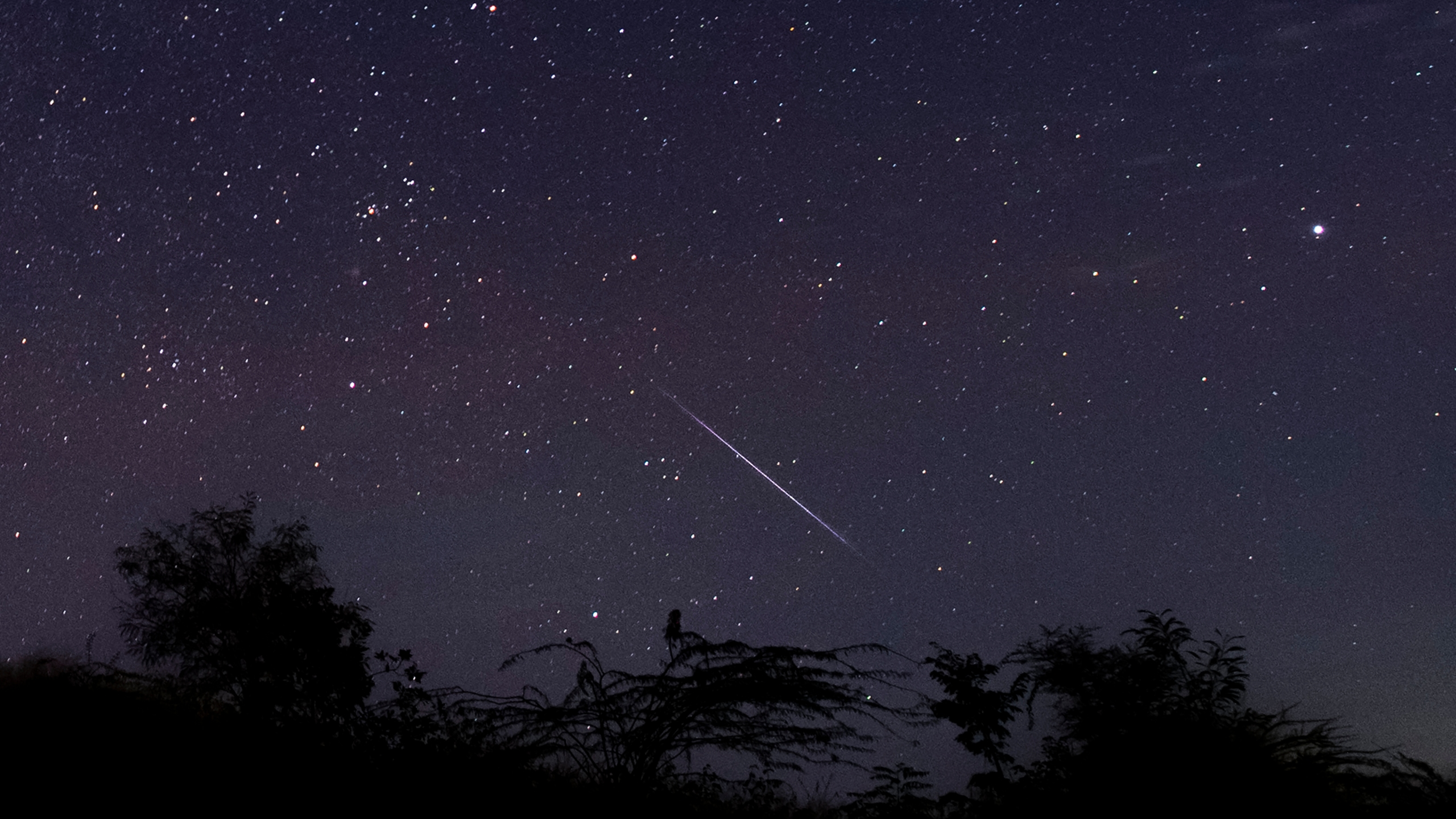 This photo taken late December 14, 2018 with a long time exposure shows a meteor streaking through the night sky over Myanmar during the Geminid meteor shower seen from Wundwin township near Mandalay city. (Credit: YE AUNG THU/AFP via Getty Images)