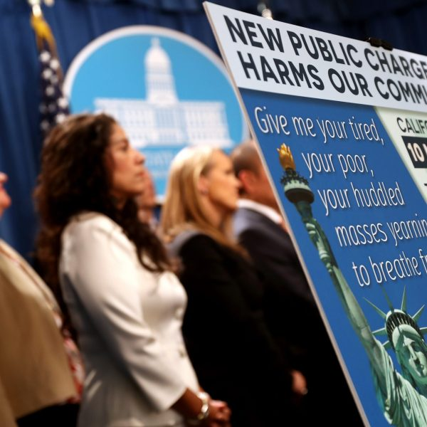 """A sign is displayed during a news conference on Aug. 16, 2019 in Sacramento announcing a lawsuit against the Trump administration over the legality of a """"public charge"""" rule that would make it difficult for immigrants on public assistance to obtain green cards. (Credit: Justin Sullivan/Getty Images)"""