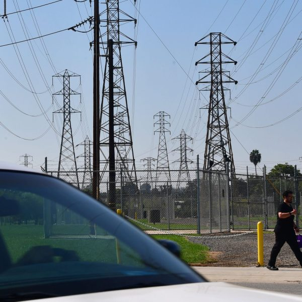 A pedestrian and motorist pass a row of power lines in Rosemead on Oct. 9, 2019. (Credit: Frederic J. Brown / AFP / Getty Images)