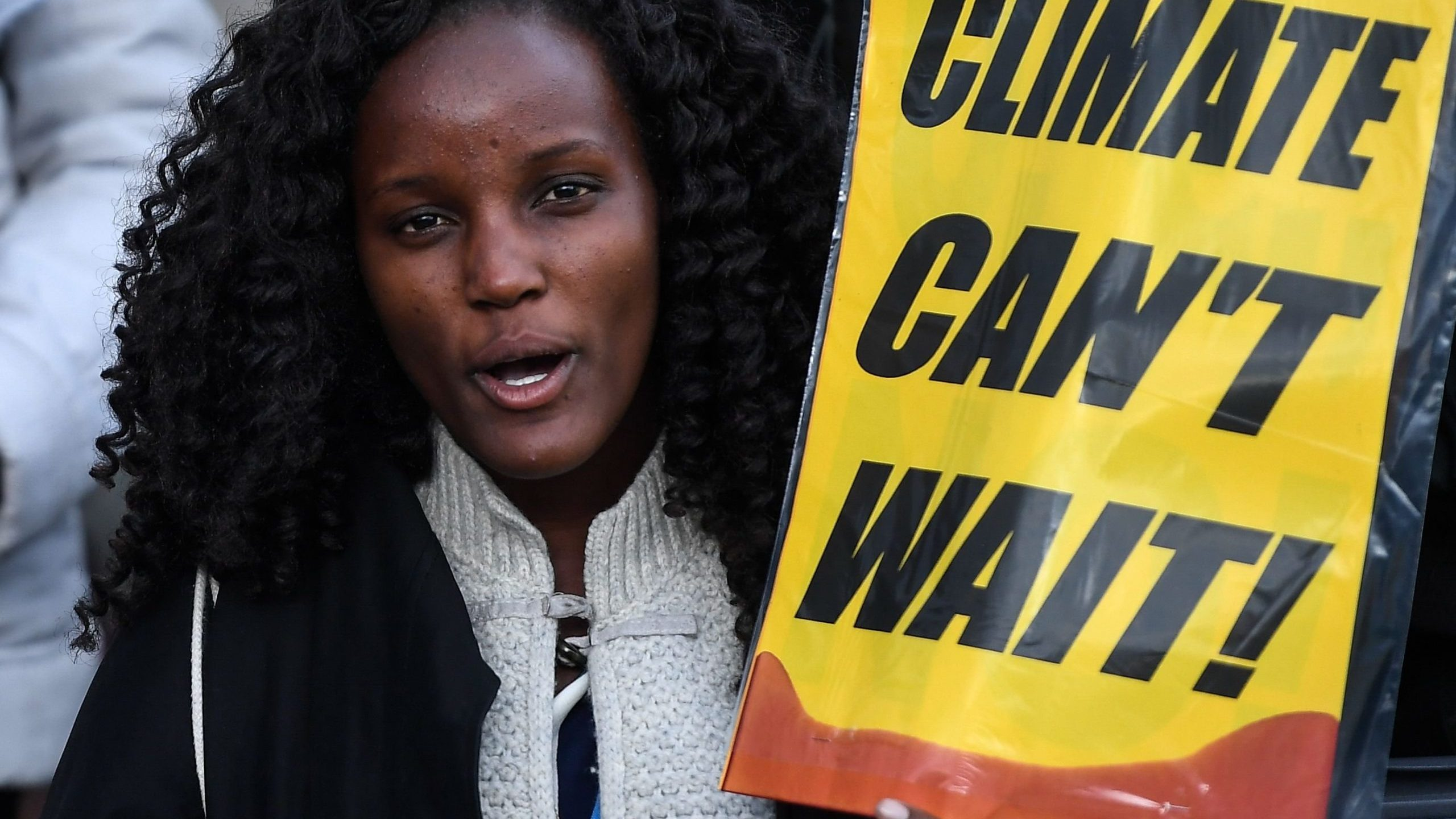 """A demonstrator holds a placard reading """"climate can't wait"""" during a protest outside the UN Climate Change Conference in Madrid, Spain, on Dec. 13, 2019. (Credit: Pierre-Philippe Marcou / AFP / Getty Images)"""