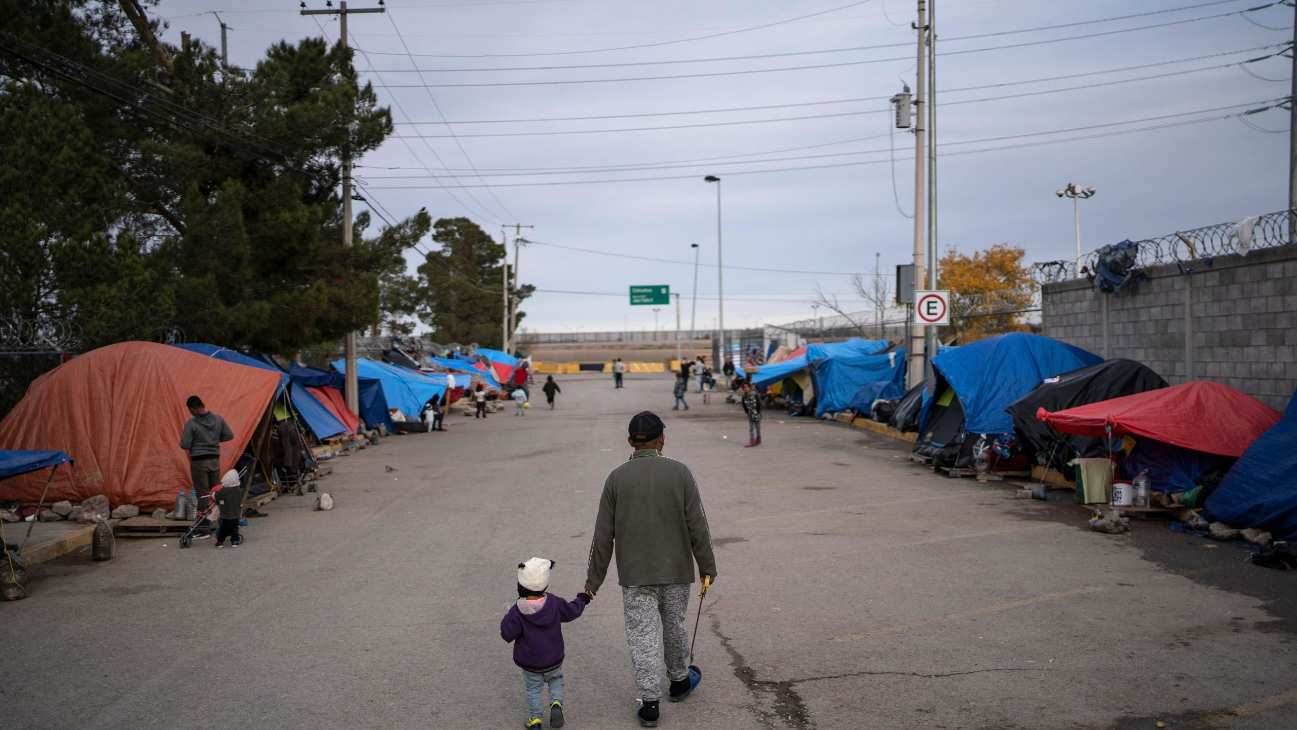 A man walks with his daughter at an asylum seekers camp near the Zaragoza bridge in Ciudad Juarez, Mexico, on Dec. 11, 2019. (Paul Ratje / AFP / Getty Images)