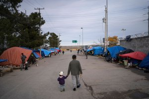 A man walks with his daughter at an asylum seekers camp near the Zaragoza bridge in Ciudad Juarez, Mexico, on Dec. 11, 2019. (Credit: Paul Ratje / AFP / Getty Images)